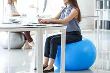 Young Businesswoman Sitting On Fitball While Working In Office