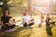 Group Of Young Women Practice Yoga In Park On Summer Sunny Morning Under Guidance Of Instructor. Group Of People Is Sitting In Lotus Pose On Grass With Eyes Closed