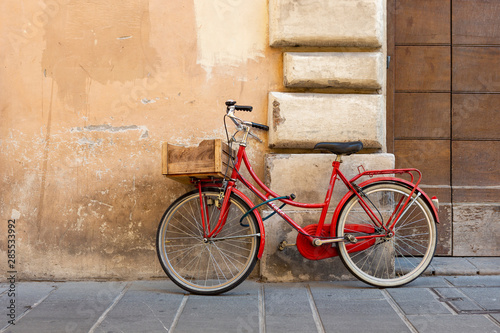 Aluminium Prints Bicycle Red classic model women's bicycle with a lock parked against the wall in the Italian city of Foligno.