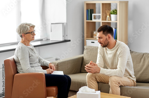Deurstickers Wanddecoratie met eigen foto psychology, mental therapy and people concept - senior woman psychologist talking to sad young man patient at psychotherapy session