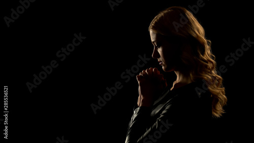 Canvas Print Blond woman praying in dark place, asking for forgiveness, sinner confession
