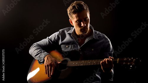 Fotografie, Tablou  Romantic male playing guitar on date, isolated on black background, hobby