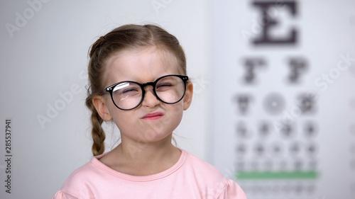 Vászonkép  Capricious little girl afraid of eyeglasses, feeling insecure, vision correction