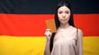 Leinwanddruck Bild - Serious Asian female showing passport against German flag background, close-up