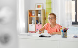 children, education and learning concept - happy student girl with book writing to notebook at home - 285539597