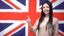 Beautiful Woman Showing Thumbs-up Against British Flag Background, Template