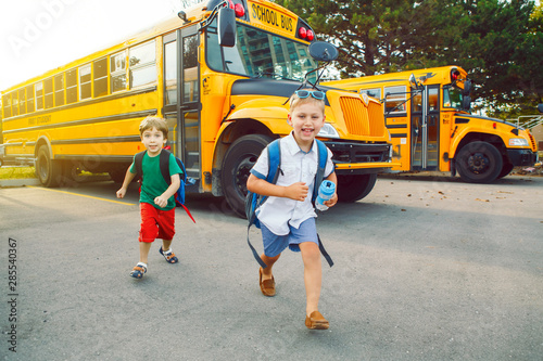 Fotografija  Two funny happy Caucasian boys students kids running near yellow bus on 1 September day