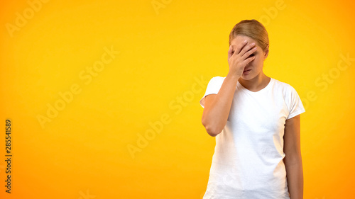 Photo  Annoyed female showing face palm gesture, covering eyes by hand, embarrassment