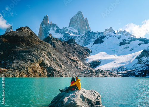 Couple in love at Mount Fitzroy. Scenic view of snowcapped mountain tops of Patagonia trek. Blue sky, turquoise lake and scenic rock landscape. Shot in Argentina. Nature, travel, adventure, hiking. - 285541907