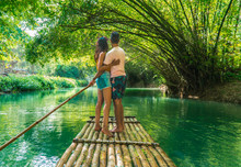 Couple In Love, On Bamboo Raft, Martha Brae. Tourist Boy Whilst On Cruise On Vacation In Montego Bay, Jamaica, Caribbean.