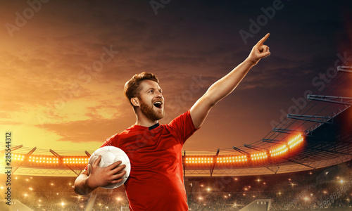 Fotografie, Tablou  Professional soccer player celebrates championship on a night soccer stadium with cheering fans