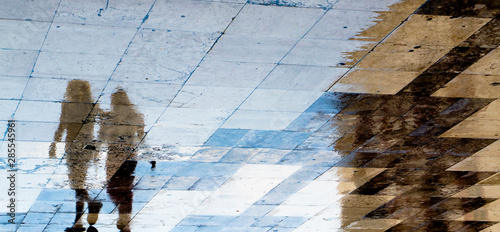Blurry reflection shadow silhouettes of  two girl friends walking on a wet city Canvas Print