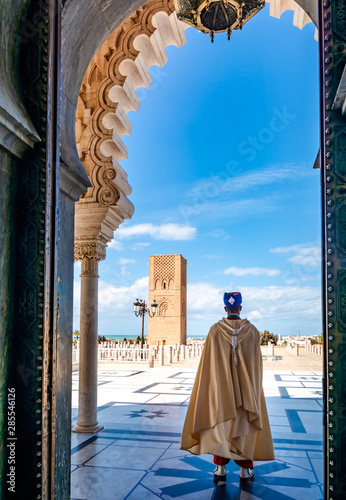 Fotomural Guard soldier in national costume at the entrance of Mausoleum of Mohammed V and square with Hassan tower in Rabat on sunny day