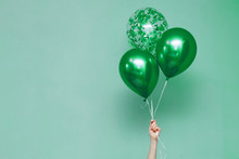 Stylish Birthday Party Or Holidays With Balloons. Three  Green Balloons On The Green Background With Copy Space For Text. Hand  Holding Three Bright Colorful Balloons Indoor.