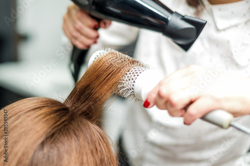 Professional hairdresser dries hair with hairdryer. Close-up of hair dryer, concept barber salon, female stylist.