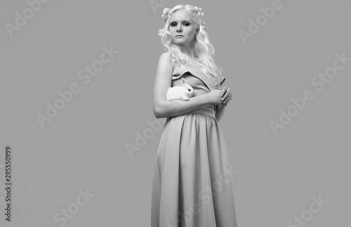 Albino blond girl in elegant dress posing with cute little rabbit