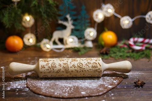 Fototapeta Rolled dough with rolling pin on wooden table covered with baking flour. obraz