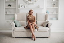 Gorgeous Pretty Lady Sitting In Luxury Apartment And Holding Hands On Knees. Beautiful Young Woman In Elegant Beige Dress Posing On White Sofa. Happy Blonde Model Relaxing After Long Working Day.