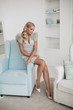 canvas print picture - Front view of beautiful blonde in blue short dress and heels sitting on dressing table and posing. Attractive woman with long legs looking down and smiling at home. Concept of beauty and glamour.