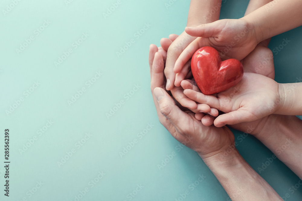 Fototapeta adult and child hands holding red heart on aqua background, heart health, charity volunteer donation, CSR concept, world heart day, world health day, family day, foster care home, organ donor day