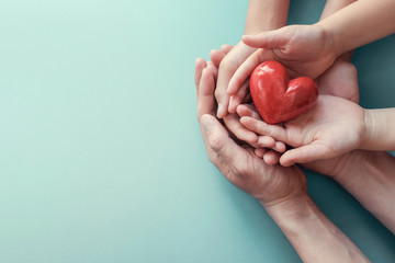 Family hands holding red heart, heart health insurance, charity volunteer donation, CSR responsibility, world heart day, world health day, family day, adoption foster care home, praying concept