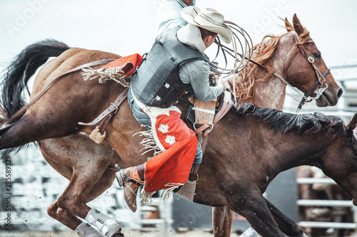 Cowboy falling off a wild horse during a bareback bronco ride in a western rodeo Wallpaper Mural