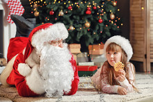 Santa Claus And Little Girl With Cookie In Room Decorated For Christmas
