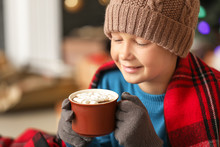 Cute Little Boy Drinking Hot Chocolate At Home On Christmas Eve