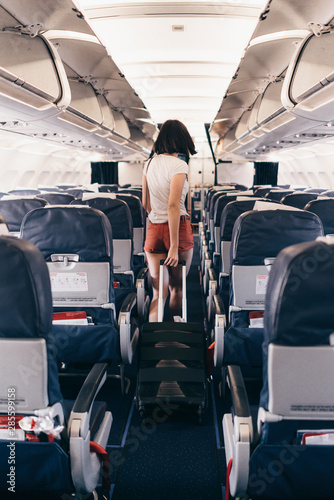 Back view of young woman walking the aisle on plane Wallpaper Mural