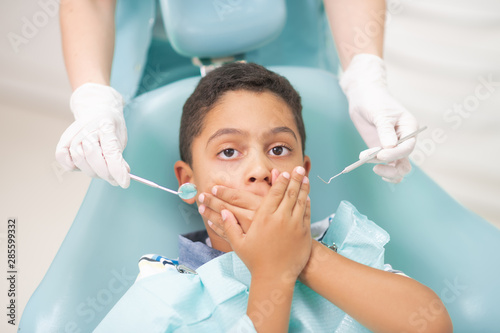 Fototapeta  Dark-eyed boy closing his mouth while feeling scared of dentist
