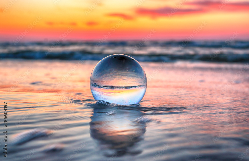 Fototapety, obrazy: Beautiful sunset on the beach in Slowinski National Park near Leba, Poland. View through a glass, crystal ball (lensball) for refraction photography. Wild, untouched nature.