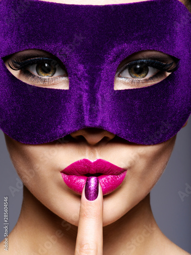 Stampa su Tela  Portrait of a beautiful  woman with purple nails and violet theatre mask on face
