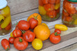 Red and yellow small marinated tomatoes in a transparent glass jar on shabby rustic table with fresh tomatoes