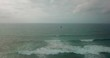 Slow aerial pan, kite surfer in stunning blue waters riding high waves.