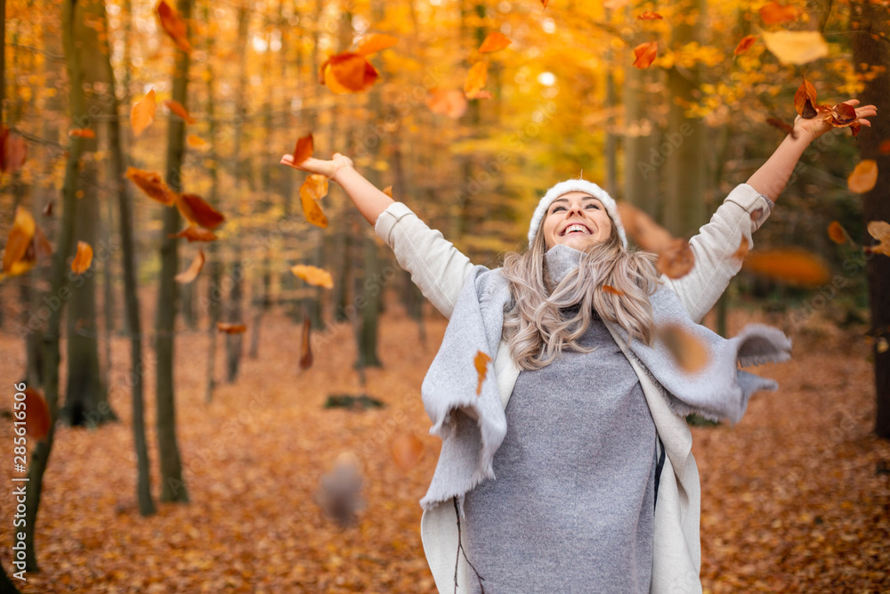 Fototapety, obrazy: Girl walking in the park in autumn and smiles with open arms