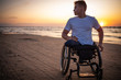 canvas print picture - Handicapped man in wheelchair and his girlfriend alone on a beach at sunset