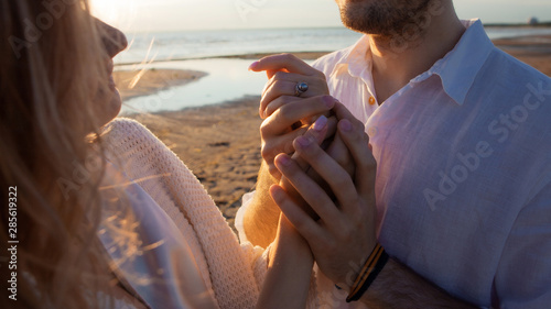 Love, romance, tenderness. A young couple sensually holding hands. The wind waves the girl's hair.