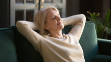 Calm Happy Old Woman Relaxing With Eyes Closed On Couch