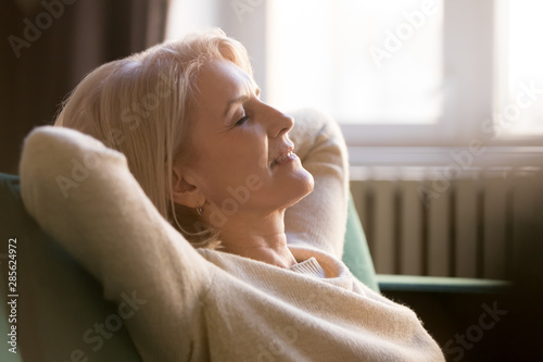 Fotografia Happy lazy old woman relaxing meditating leaning on comfortable sofa