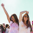 Smiling young women wearing sunglasses dancing at holi festival