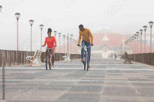 Couple riding bicycle at promenade on a sunny day