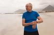 Happy senior man using smartwatch at the beach