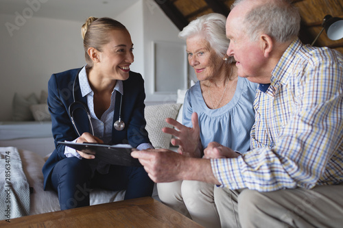 Fotomural  Female doctor and senior couple discussing over clipboard