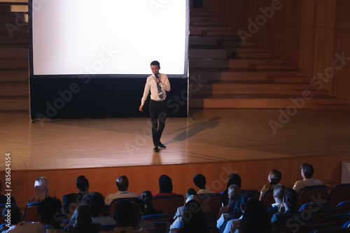 Businessman standing and giving presentation in auditorium
