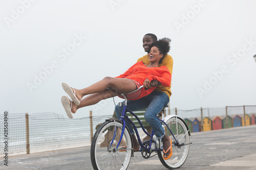 Couple enjoying at bicycle while riding at pavement