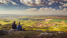 Two People (couple - Man And Woman) Sitting On A Mountain On A Stone And Looking Into The Valley On Beautiful Autumn Landscape With Village, Vineyards And Fields. Blue Sky, White Clouds. Palava, Czech