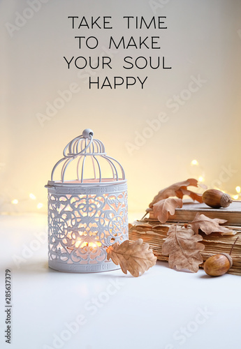 take time to make your soul happy - inspiration quote. candle holder, old books, autumn leaves and acorns. beautiful cozy autumn still life. fall season concept. shallow depth, soft selective focus