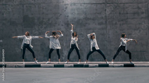Multiple Exposure Shot of a Cool Cloned Young Blond Woman with Long Hair Poses in Three Dance Poses on a Street Next to a Big Concrete Wall. She's Wearing a Striped White Shirt and Dark Jeans. - 285644949