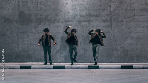 Photo Multiple Exposure Shot of a Cool Cloned Young Hipster Man with Long Hair Stands in Dance Poses on a Street Next to a Big Concrete Wall