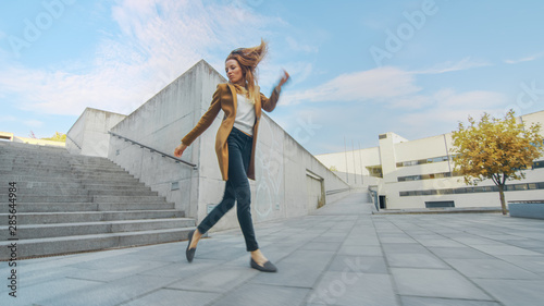 Fotografie, Obraz  Cheerful and Happy Young Woman Actively Dancing While Walking Down the Stairs